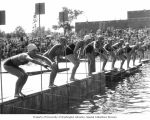 Ten girl swimmers lining up to start a race at Greenlake while a crowd watches, Seattle,...