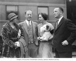 Swimmer Helene Madison holding a stuffed dog and standing outside a  train with her parents and...