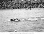 Swimmer Helene Madison swimming in a lake while a crowd watches in the background,Washington...