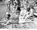 Coach Ray Daughters and swimmer Helene Madison on a dock giving swim instruction to four children,...