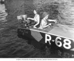 Two women in a small speedboat on a lake, starting the motor, probably Washington, ca. 1929-1932