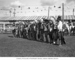Native American men in traditional dress lined up in an arena, probably Washington State, ca....