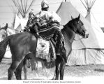 Native American woman and small child in traditional dress on a horse  in front of teepees,...