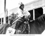 Native American woman and small child in traditional dress on a horse, probably Washington State,...