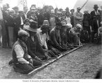 Eight Native American men holding sticks kneeling in front of a long stick while a crowd watches...