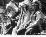 Four seated Native American men in full headdress and traditional dress, Puyallup, Washington, ca....