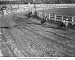 Three motorcyclists racing around a fenced dirt track, probably Washington State, ca. 1929-1932