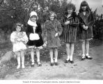 Five little girls wearing fur coats standing side by side in a line, probably Washington State,...