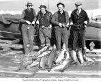 Four men standing in front of a fishing boat on a dock, holding a net full of salmon, Washington...