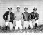 Four jockeys kneeling in the grass in front of a stable, Washington State, ca. 1929-1932