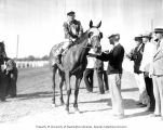 Jockey and racehorse with a group of men at a track, Washington, ca. 1929-1932