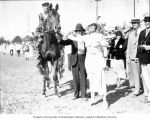 Man and woman standing next to a winning jockey and horse, Washington, ca. 1929-1932