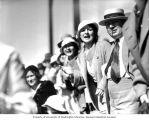 Man and woman surrounded by other horse race attendees cheering in the stands, Washington State,...