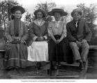 Frank Bonds sitting on fence with three girls, Sumas, October, 1909