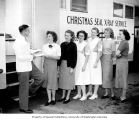 Walter John Kain, x-ray technician, distributing forms to a line of women outside an x-ray truck,...