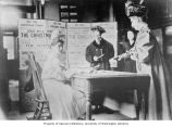 Nurse selling stamps at table with posters during the Christmas Seals Campaign, ca. 1919