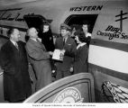 Tacoma Mayor C.V. Fawcett standing at door of a Western Airlines airplane and receiving mistletoe...