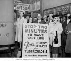 People standing by sign advertising free chest x-ray screening near the Crown Hill Gift Shop,...