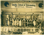 Groups of Japanese students at the Tanaka School of Dressmaking holding scrolls on stage in front...