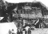 Native American women, possibly Makah, with fish-drying racks and smokehouse on the beach, Neah...