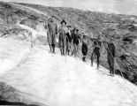 Seven hikers standing in snow with alpenstocks, probably at Mt. Rainier, ca. 1920-1945