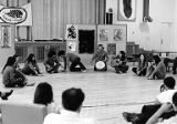 El Teatro del Piojo members sitting in a circle playing instruments and singing, in an unknown...