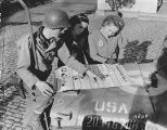 Soldier and two young women reading an information broadsheet laid out on the hood of a jeep,...