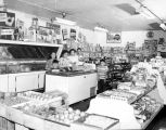 Owner and family of the Belmont Food Market standing by the counter, 506 Main St., Seattle, July...