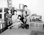 Joe Nam Kun and family posing for a photograph in the living room of their home, probably Seattle,...