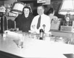 Bartender and waitress posing behind the counter of the Banquet Tavern and Tally Ho, 1239 Jackson...