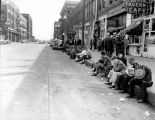 Men sitting on the curb in front of the Occidental Tavern Cafe, 207 Occidental Ave., Seattle, ca....
