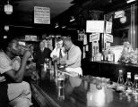 Bartenders serving beer with patrons drinking and socializing at a bar, Seattle, ca. 1950's