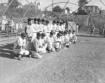 Western Giants baseball team posing with two trophies at a local park, ca. 1950