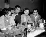 Elmer Ogawa, standing, and three friends playing dice at a local bar, Seattle, ca. 1950s
