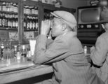 African-American man sitting at the counter of a local bar, Seattle, ca. 1950's