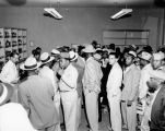 Crowd of African-American men lining up to purchase goods at a local liquor store, ca. 1950's