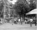 Men women and children at a local park enjoying the ferris wheel and carousel, Seattle, ca. 1951