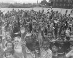 Large group of children waving to the camera in a school playground, March 2, 1952
