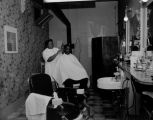 African-American barber cutting the hair of a patron in a local barber shop, ca. 1950's