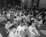 Large group of mostly African-American and Asian-American school children seated on the floor of...