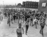 Large group of children running across a school playground, March 2, 1952