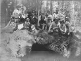Mazama Club members sitting on rocks above a cave entrance in the forest on an outing to Mount...