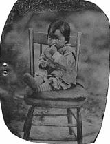 Spokane Indian toddler sitting on chair with hand-tinted pink cheeks and socks, ca. 1870's