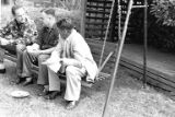 Three men sit with food on swinging bench at a Hogenauer and Gourley family members picnic, ca....