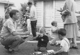 Children and adults eating on lawn at a Hogenauer and Gourley family members picnic, ca. 1945