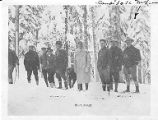 Walter McLean with ski group in snow field near woods, n.d.