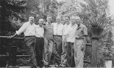 Seven men on cabin deck in the woods, 1942