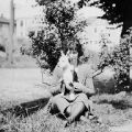 Babe Harris sitting in front of tree with a dog, ca. 1920s