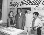 Local boxer Eddie Cotton and friends cut a birthday cake in celebration of Mr. Cotton's birthday,...