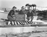Participants in the International Sportsman's Club Salmon Derby holding the derby sign while...